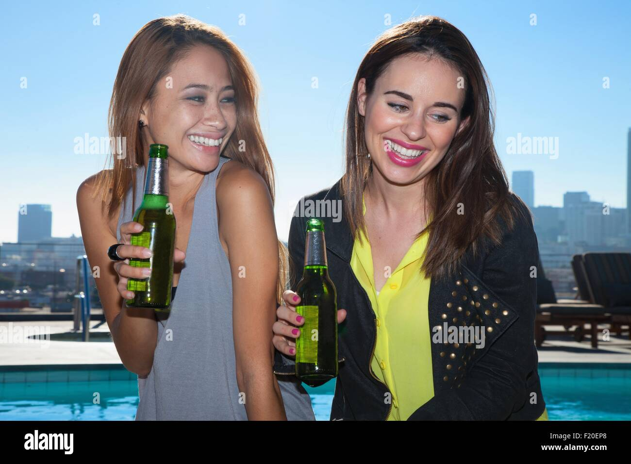Two young adult female friends drinking beers at rooftop bar with Los Angeles skyline, USA - Stock Image