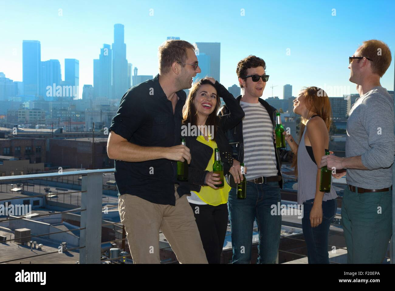 Five adult friends flirting and drinking beer at rooftop bar with Los Angeles skyline, USA - Stock Image