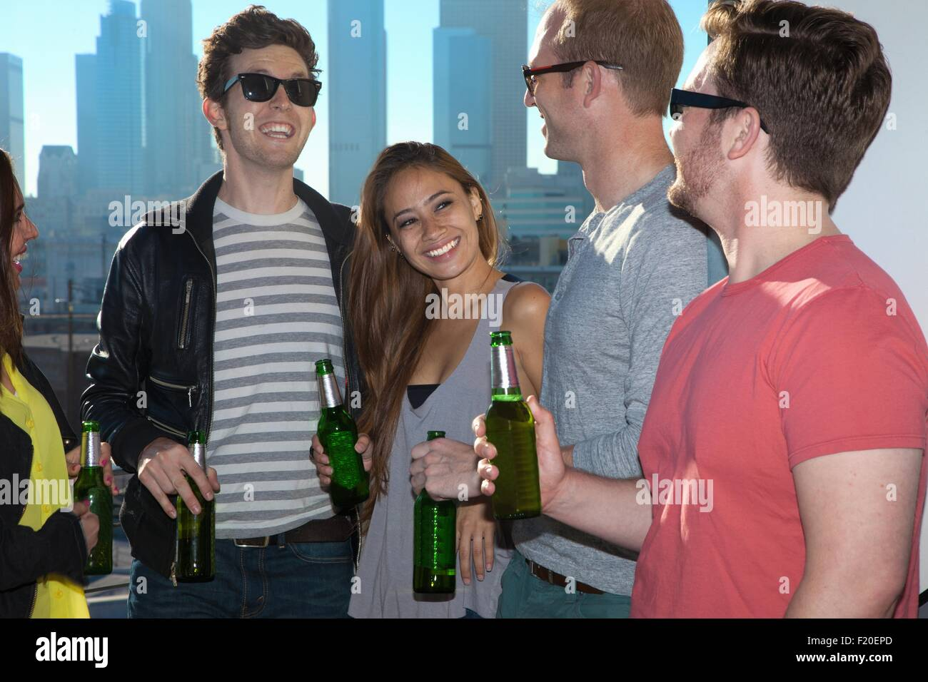 Five adult friends drinking beer at rooftop bar with Los Angeles skyline, USA - Stock Image