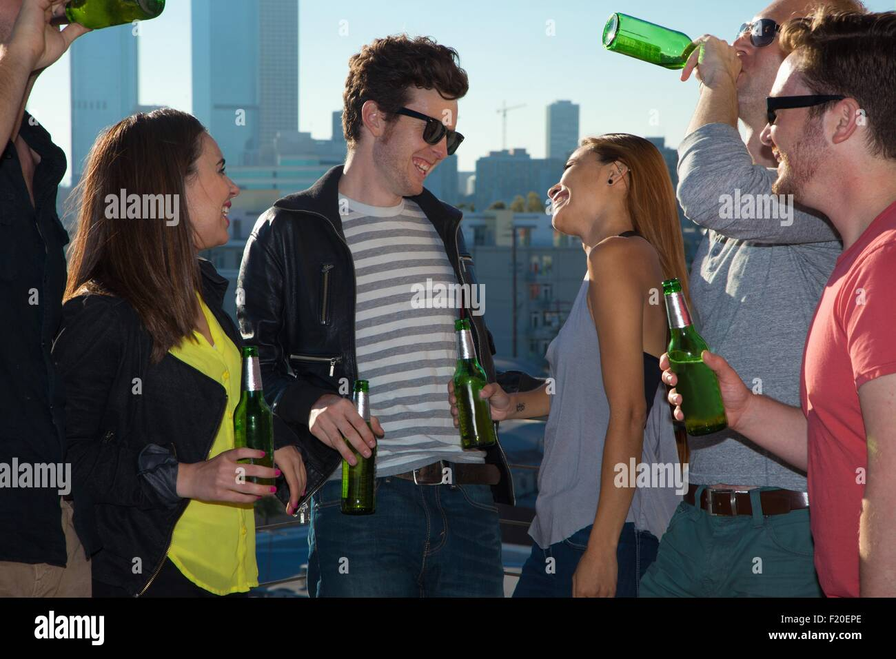Six adult friends flirting and drinking beer at rooftop bar with Los Angeles skyline, USA - Stock Image