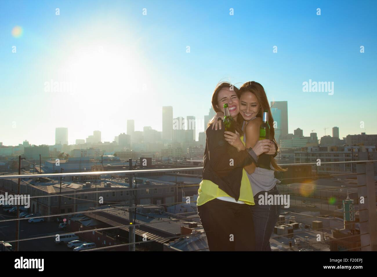 Portrait of two young women hugging and drinking beers at rooftop bar with Los Angeles skyline, USA - Stock Image