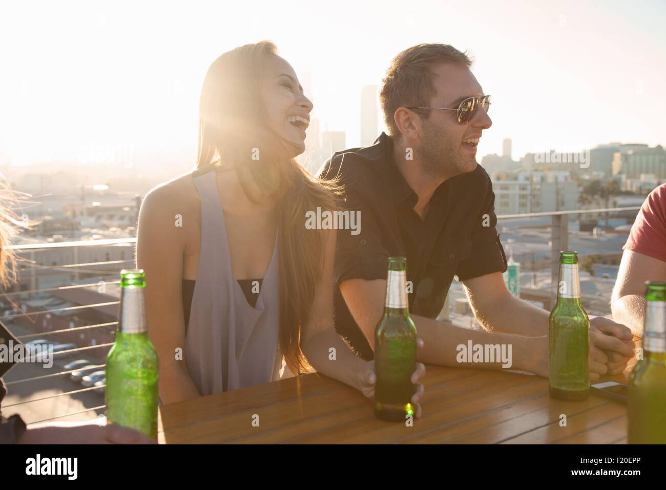 Two adult friends drinking beer at rooftop bar table with Los Angeles skyline, USA - Stock Image