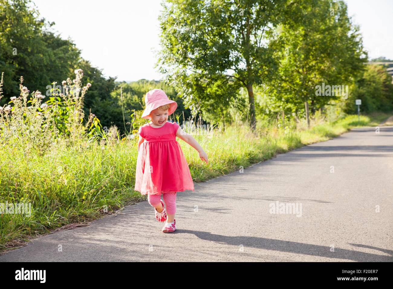 Female toddler watching her shadow toddling along rural road - Stock Image