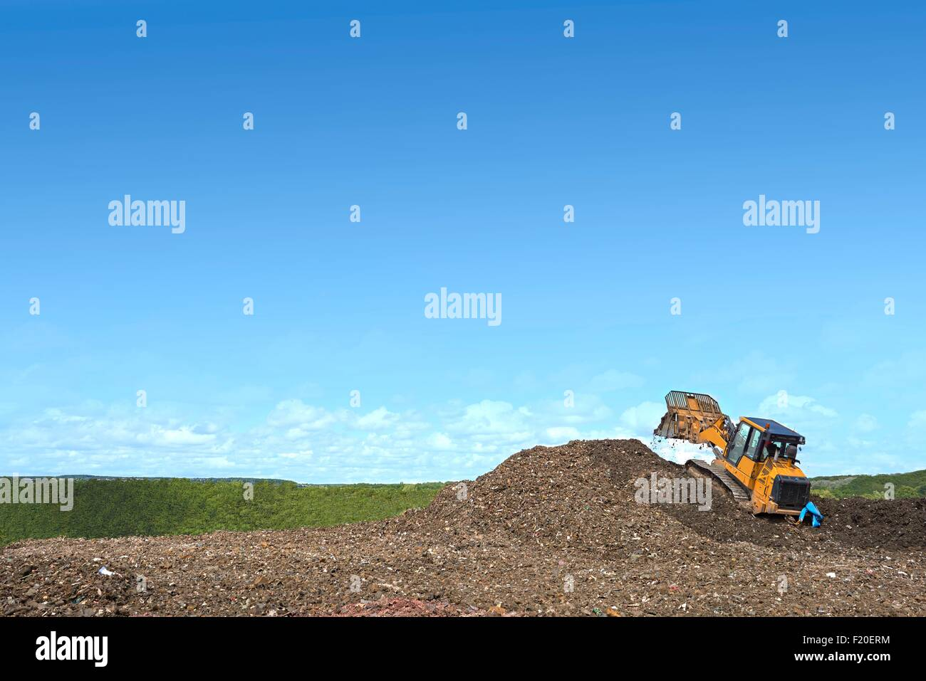 Digger on mound burying waste on landfill site - Stock Image