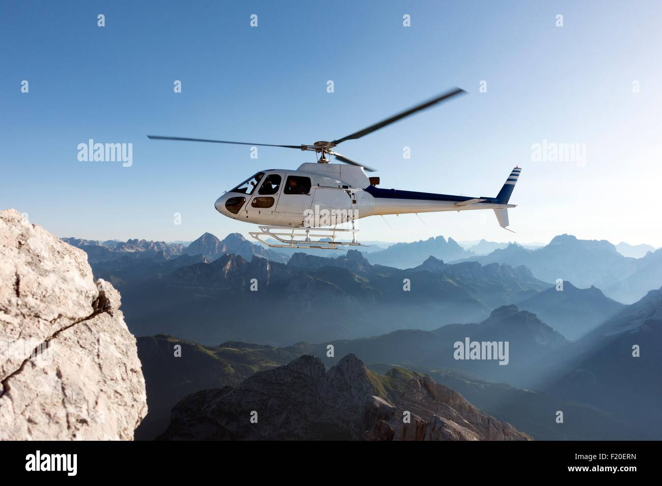 Helicopter transporting BASE jumpers to summit, Dolomites, Italy - Stock Image