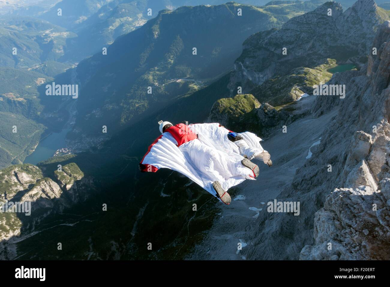 Two male BASE jumpers wingsuit flying from mountain, Dolomites, Italy - Stock Image