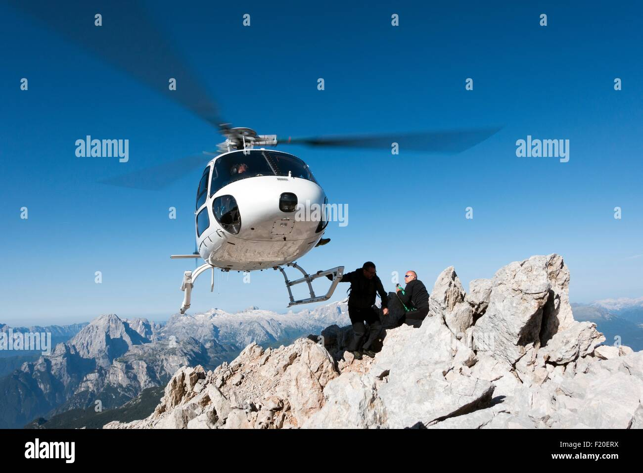 Helicopter dropping BASE jumpers on mountain, Dolomites, Italy - Stock Image
