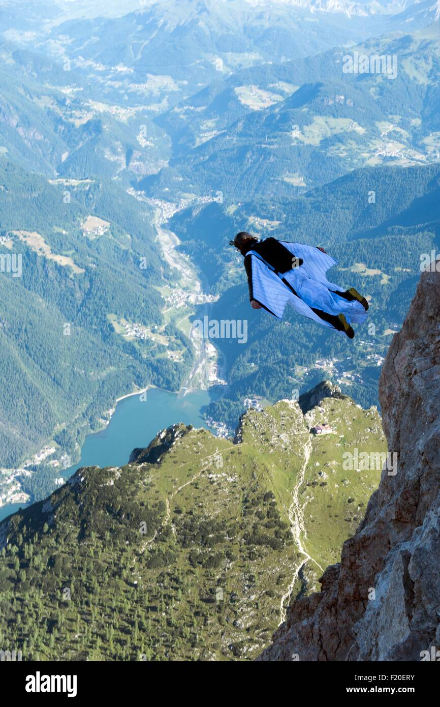 Male BASE jumper wingsuit flying over valley, Dolomites, Italy - Stock Image