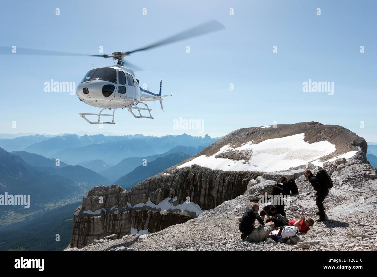 BASE jumpers preparing wingsuits on mountain summit, Dolomites, Italy - Stock Image