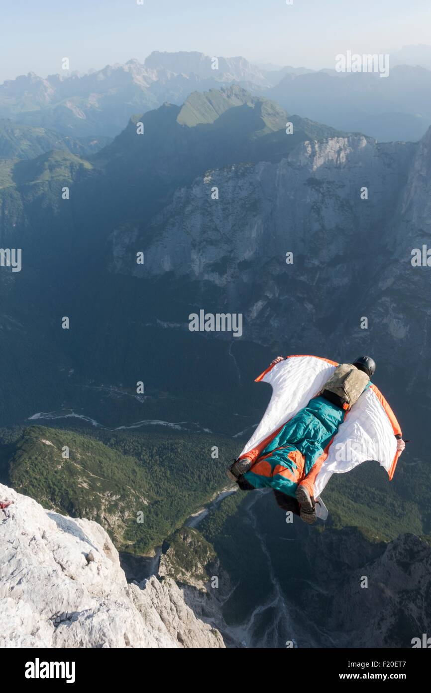 Male BASE jumper wingsuit flying from mountain, Dolomites, Italy - Stock Image