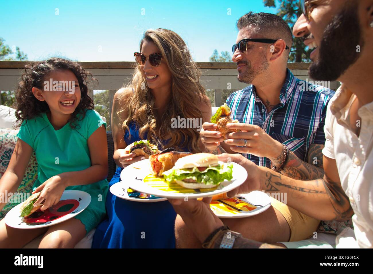 Mid adult family and daughter eating barbecue food in garden - Stock Image