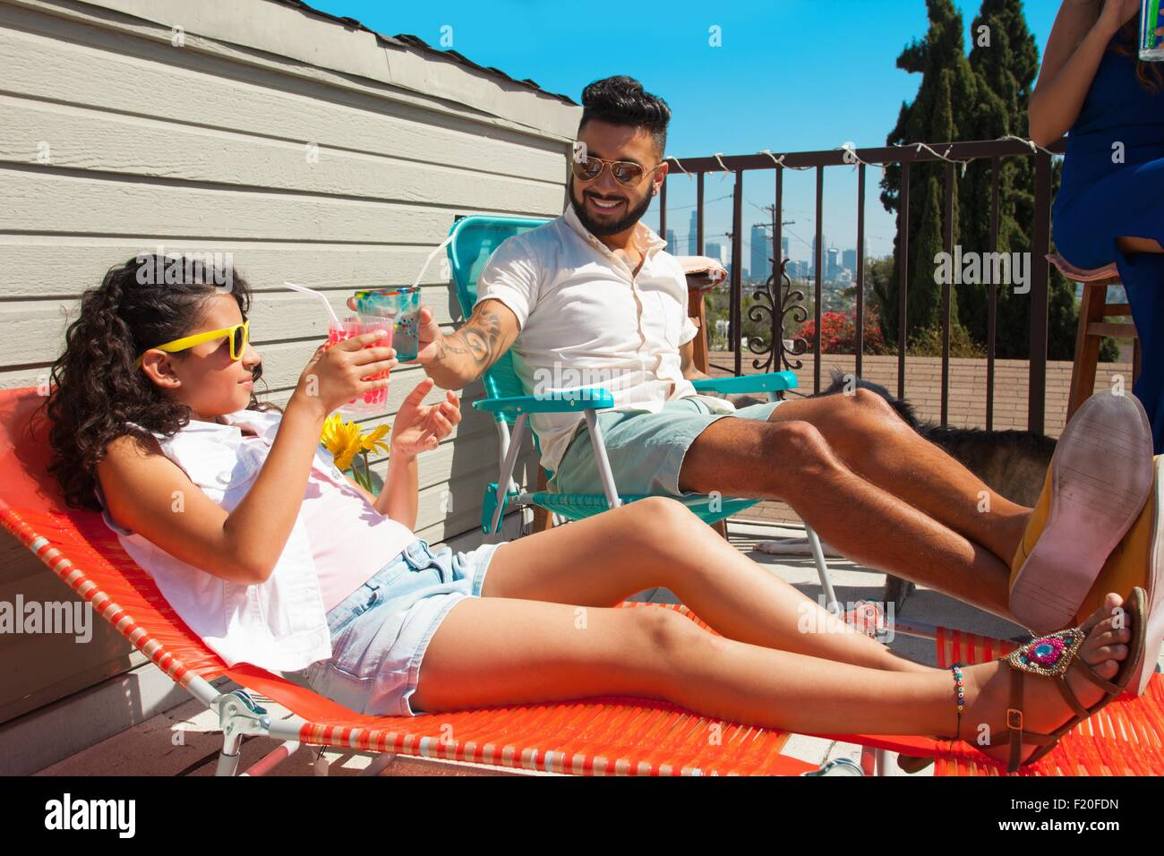 Girl and her father toasting with juice drink on patio - Stock Image