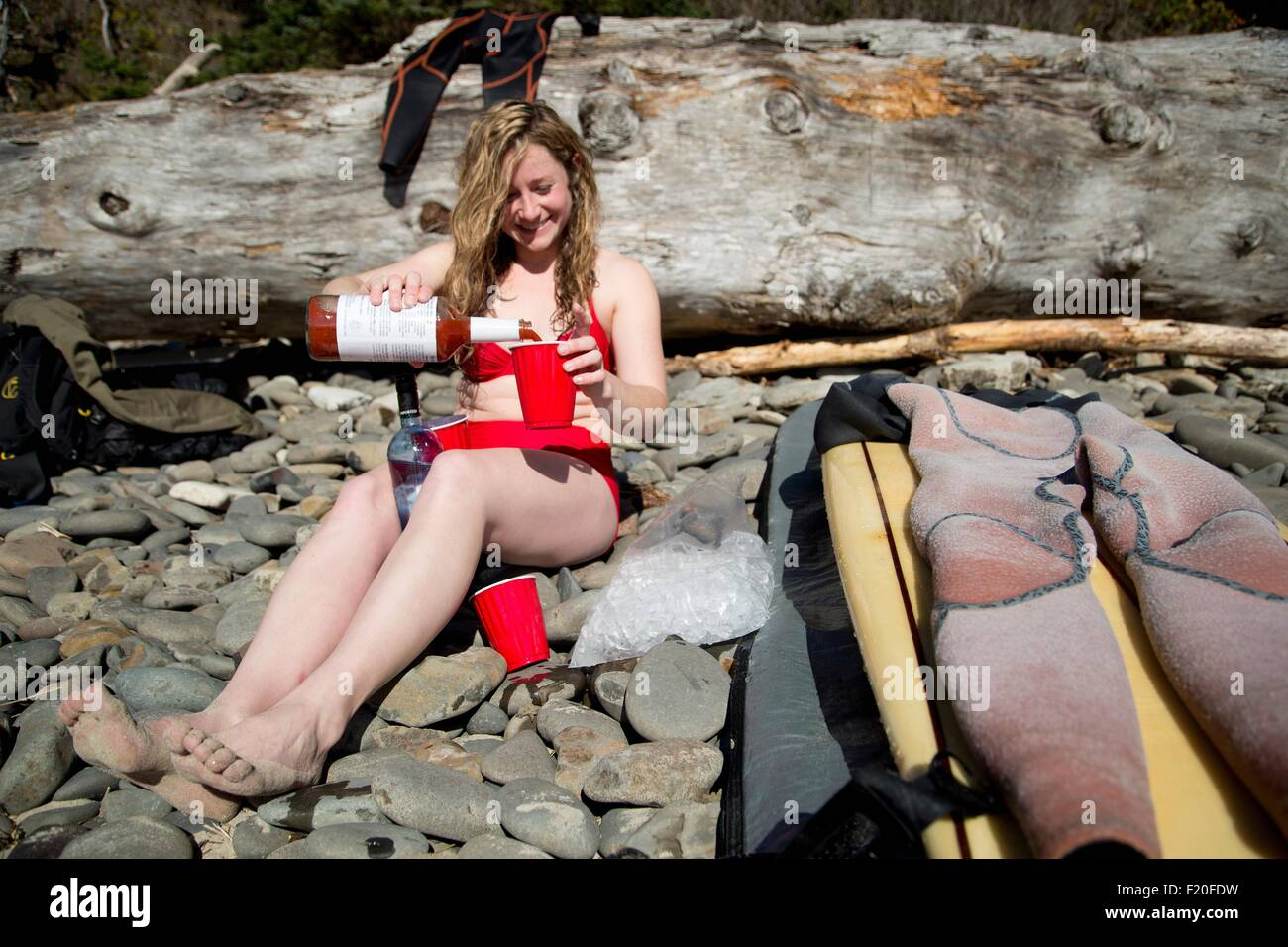 Young woman sitting on rocky beach, pouring drink, Short Sands Beach, Oregon, USA - Stock Image
