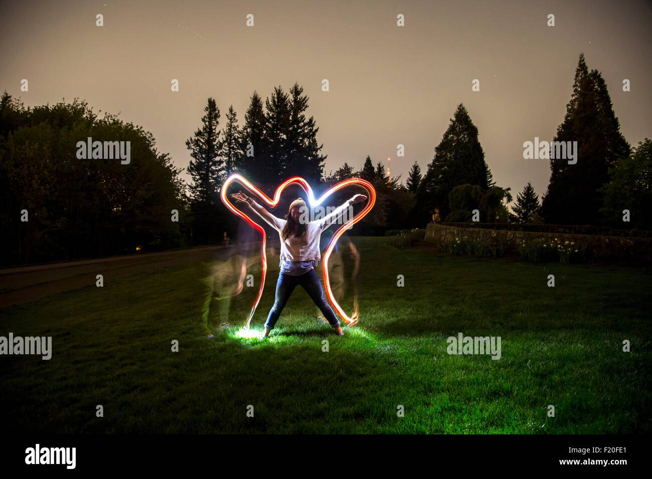 Young woman, standing in field at dusk, arms and legs outstretched in star shape, light trail tracing body shape - Stock Image