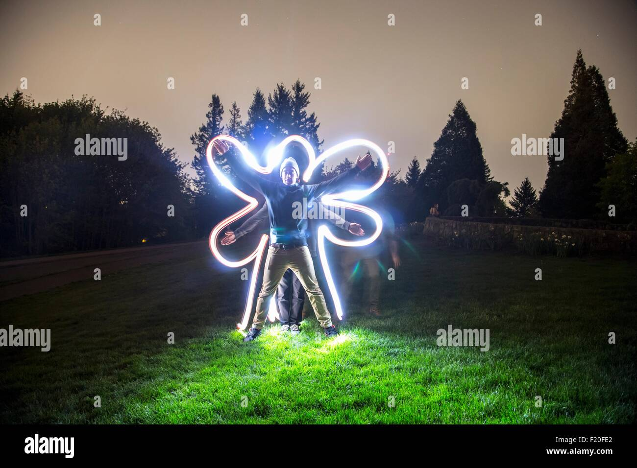 Two men standing together in field at dusk, creating star shape with bodies, friend tracing body shape with light - Stock Image