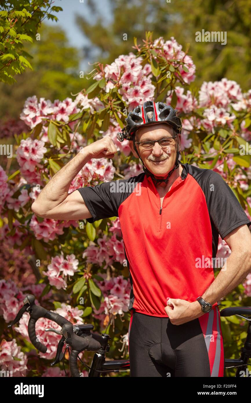 Portrait of senior man, flexing muscles, ready to use bicycle - Stock Image