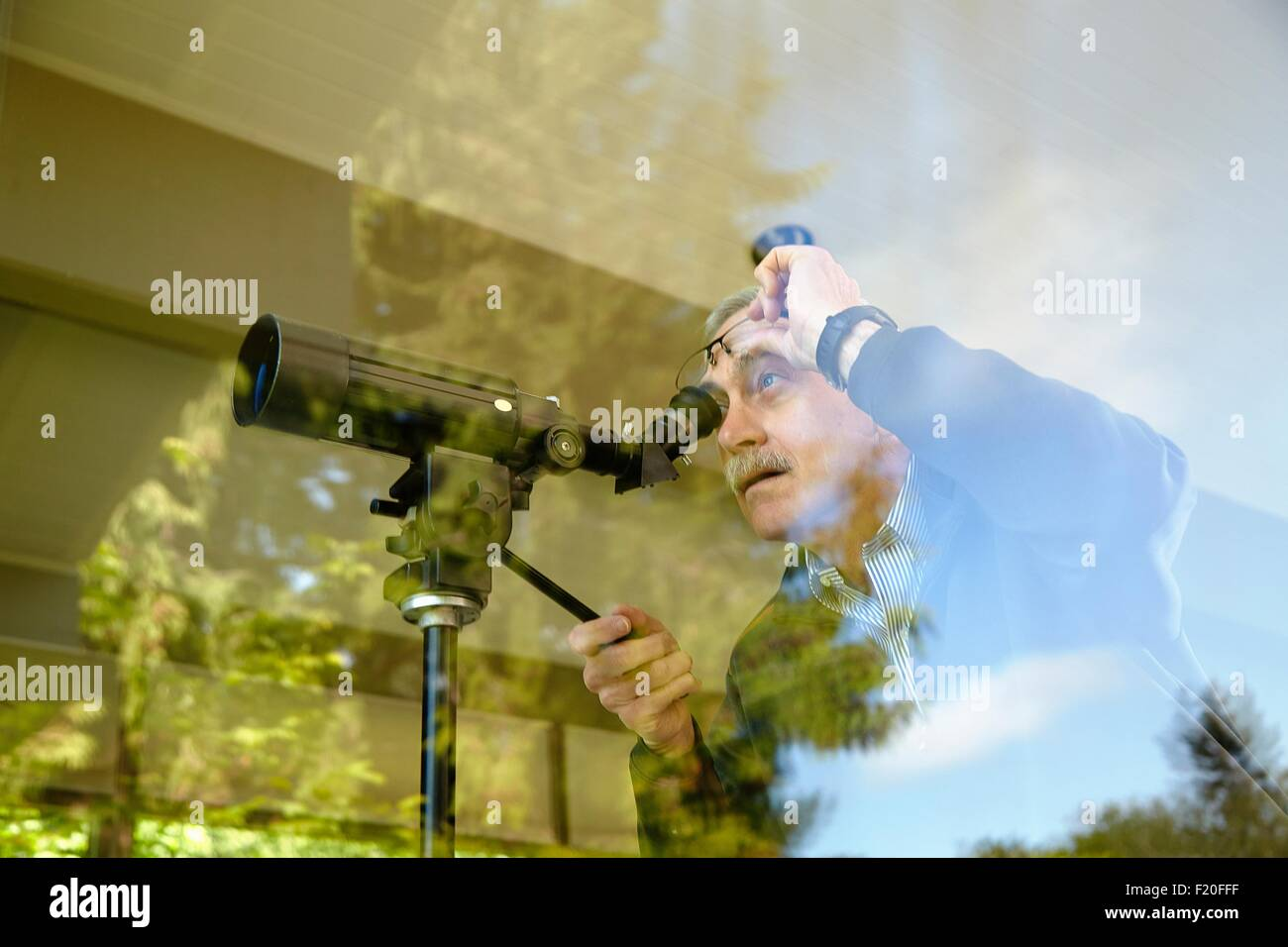 Senior man at home, using telescope through window - Stock Image