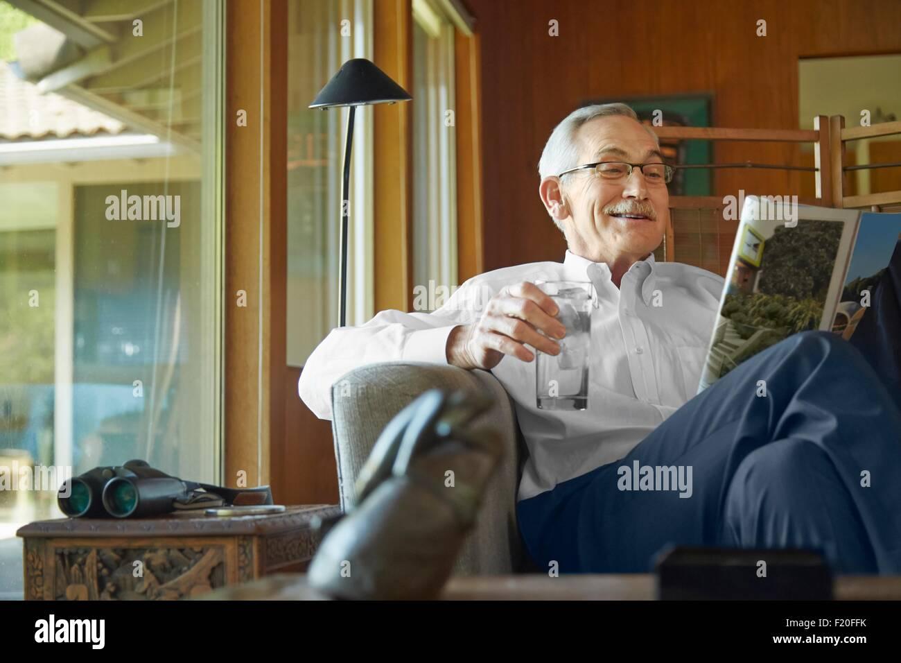 Senior man at home, reading magazine - Stock Image