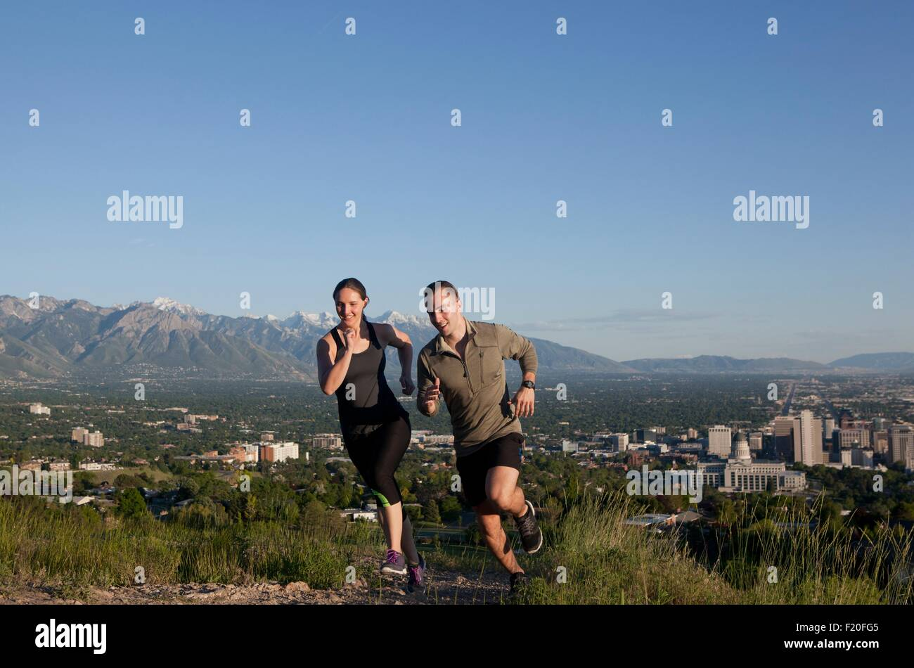 Young female and male runners racing along track above city in valley - Stock Image
