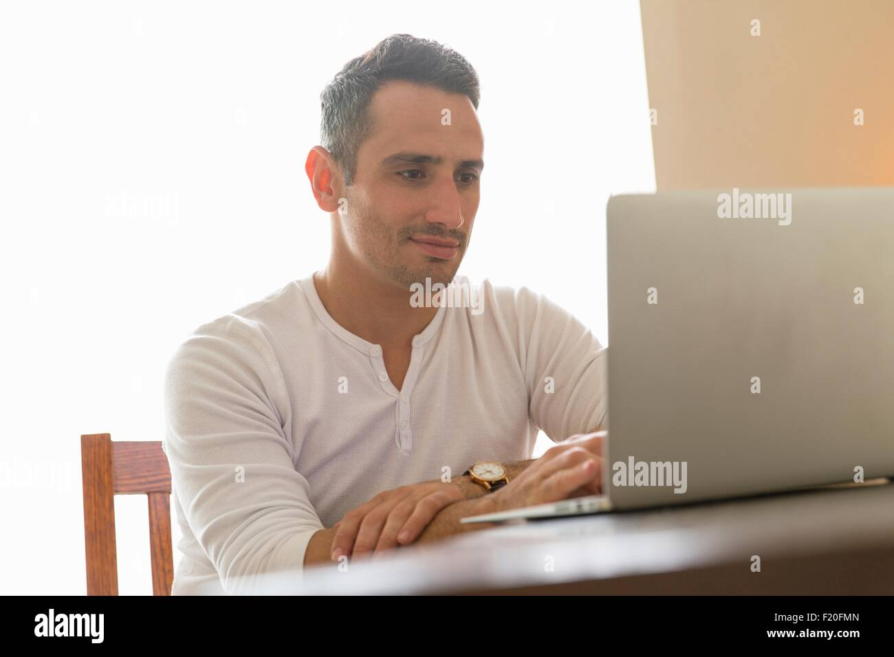 Mid adult man sitting at desk, using laptop - Stock Image