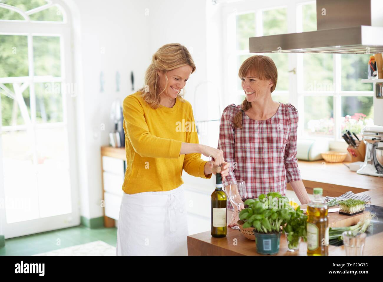 Woman opening wine bottle in kitchen - Stock Image
