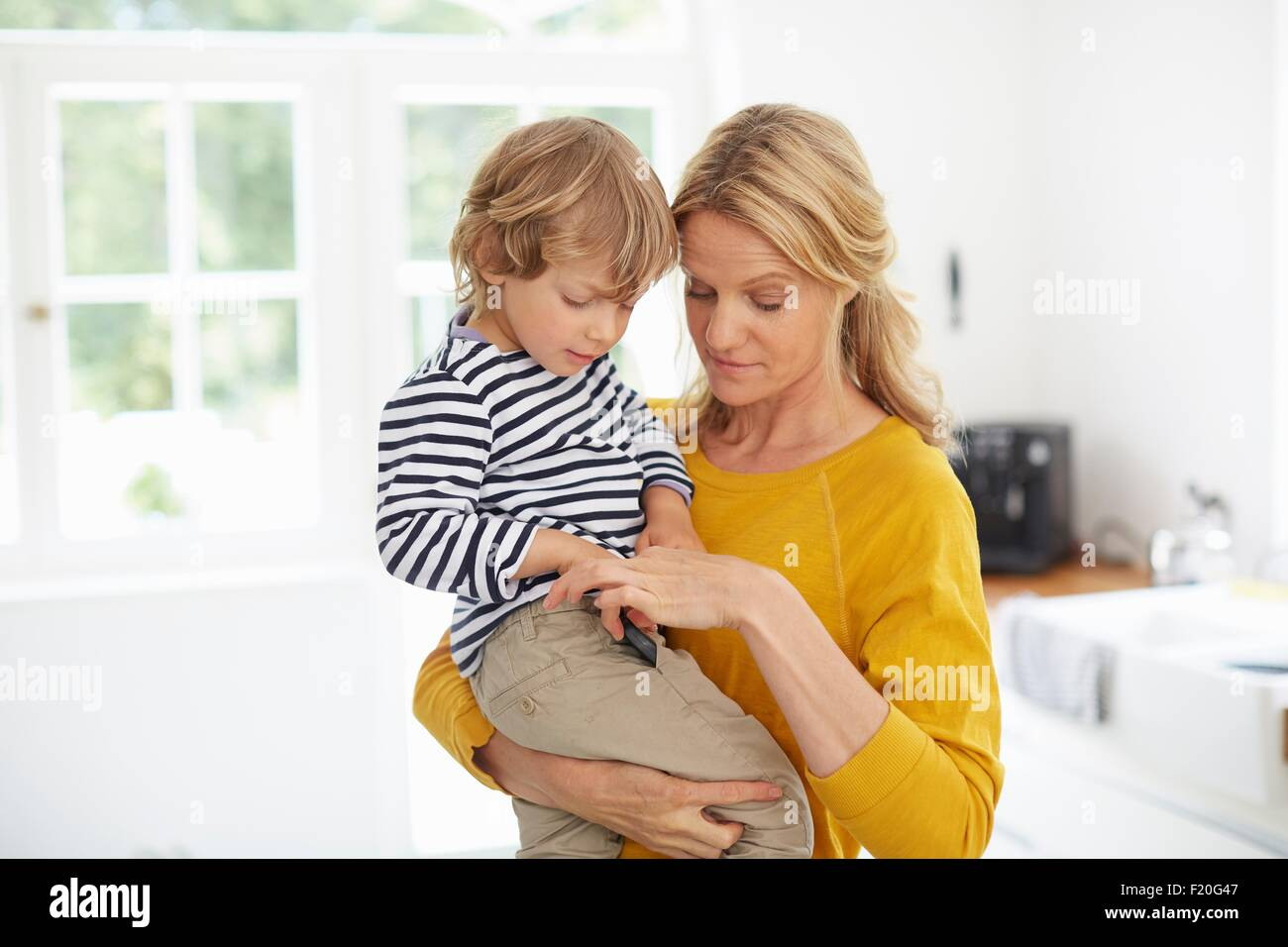 Mother carrying son in kitchen - Stock Image