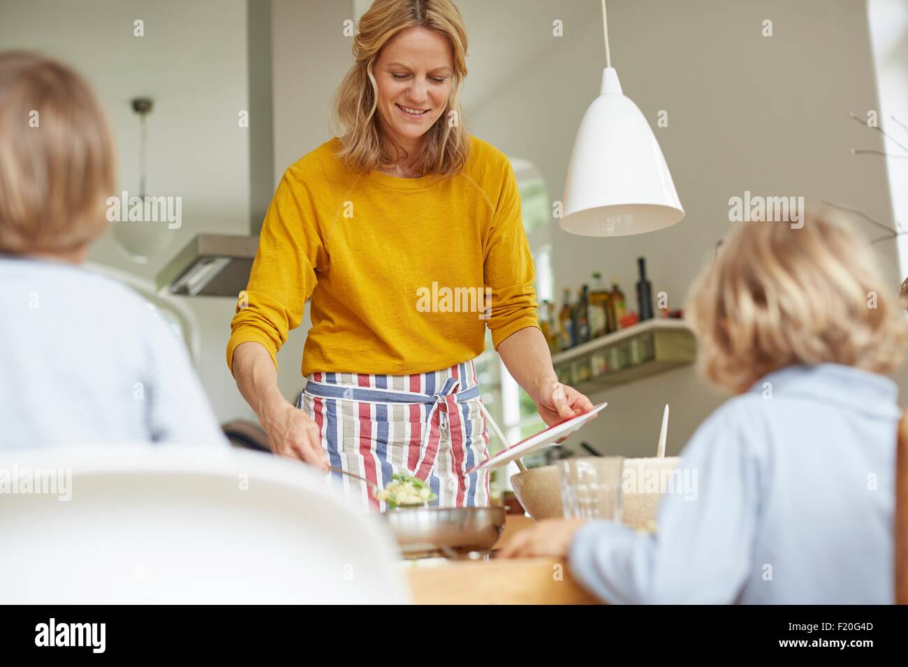 Woman serving meal at dining table - Stock Image