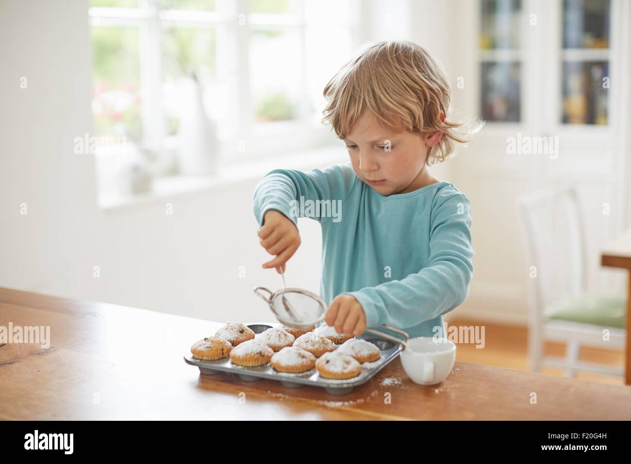 Boy making cupcakes in kitchen - Stock Image