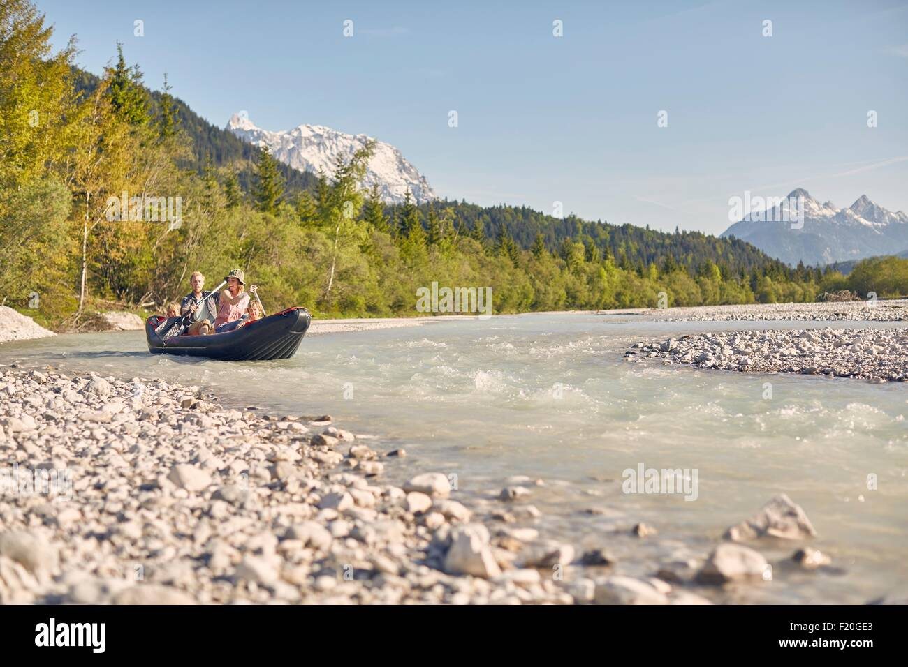 Family using paddles to steer dinghy on water, Wallgau, Bavaria, germany - Stock Image