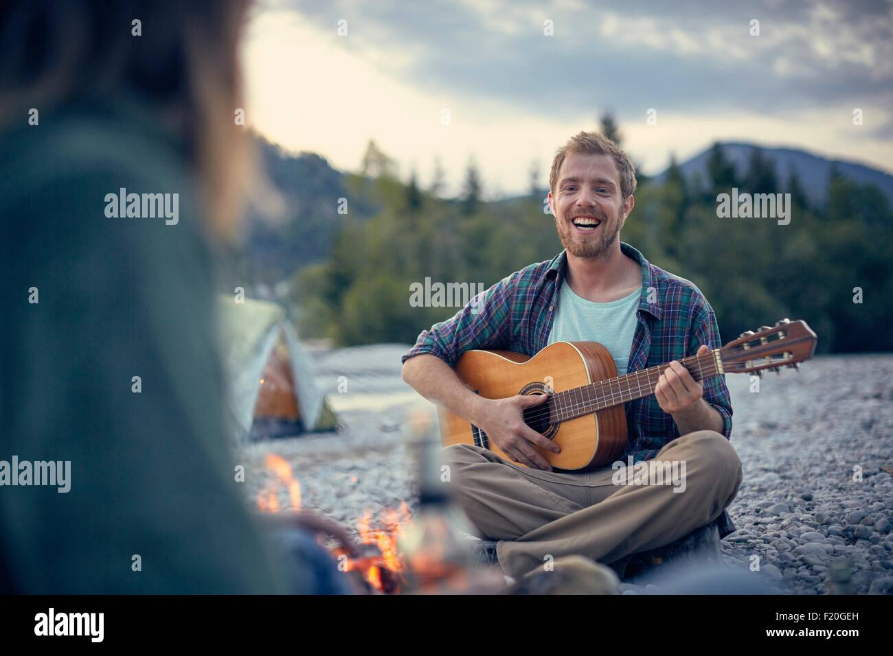 Front view of young man sitting by campfire playing guitar - Stock Image
