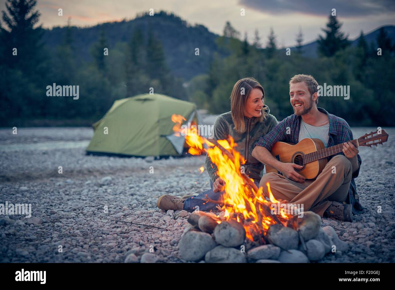 Young couple sitting by campfire playing guitar - Stock Image