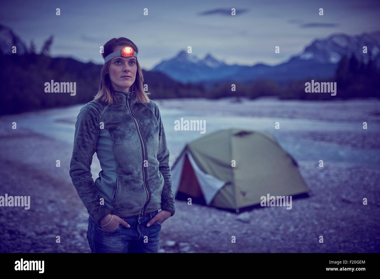 Young woman wearing headlamp, hands in pockets, looking away, Wallgau, Bavaria, Germany - Stock Image