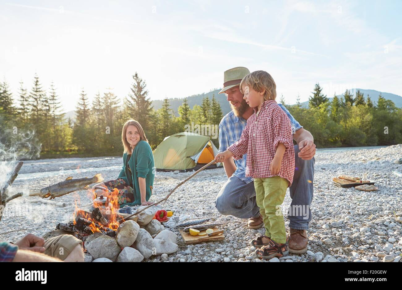 Boy and mid adult man poking campfire with branch - Stock Image