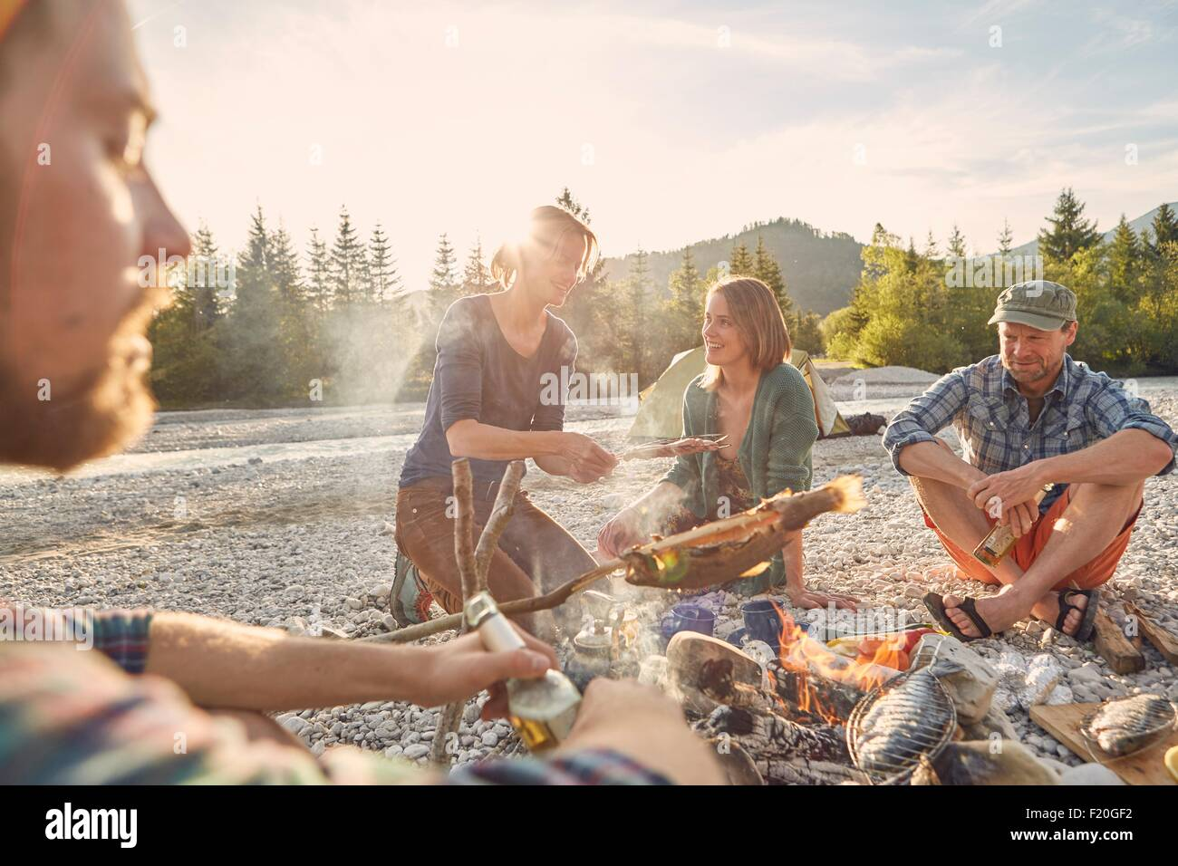 Adults sitting around campfire cooking fish - Stock Image