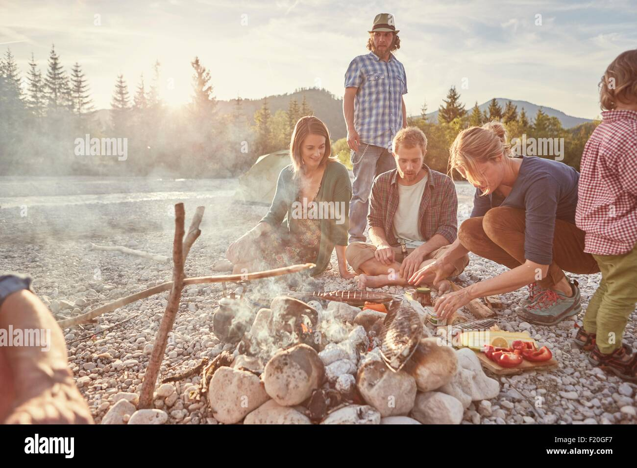 Family sitting around campfire preparing food - Stock Image