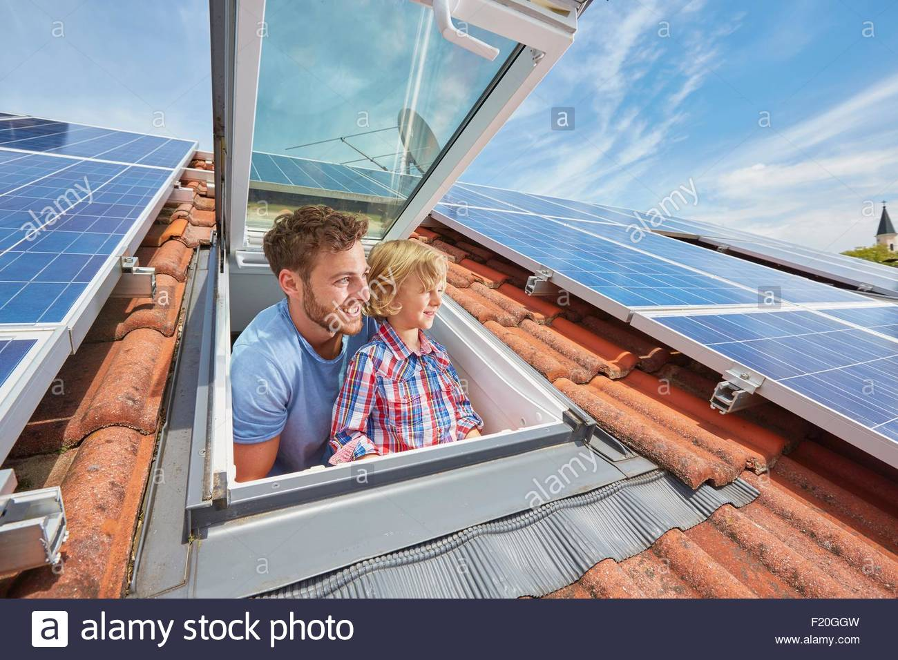 Father and son looking out of window of solar panelled roof - Stock Image