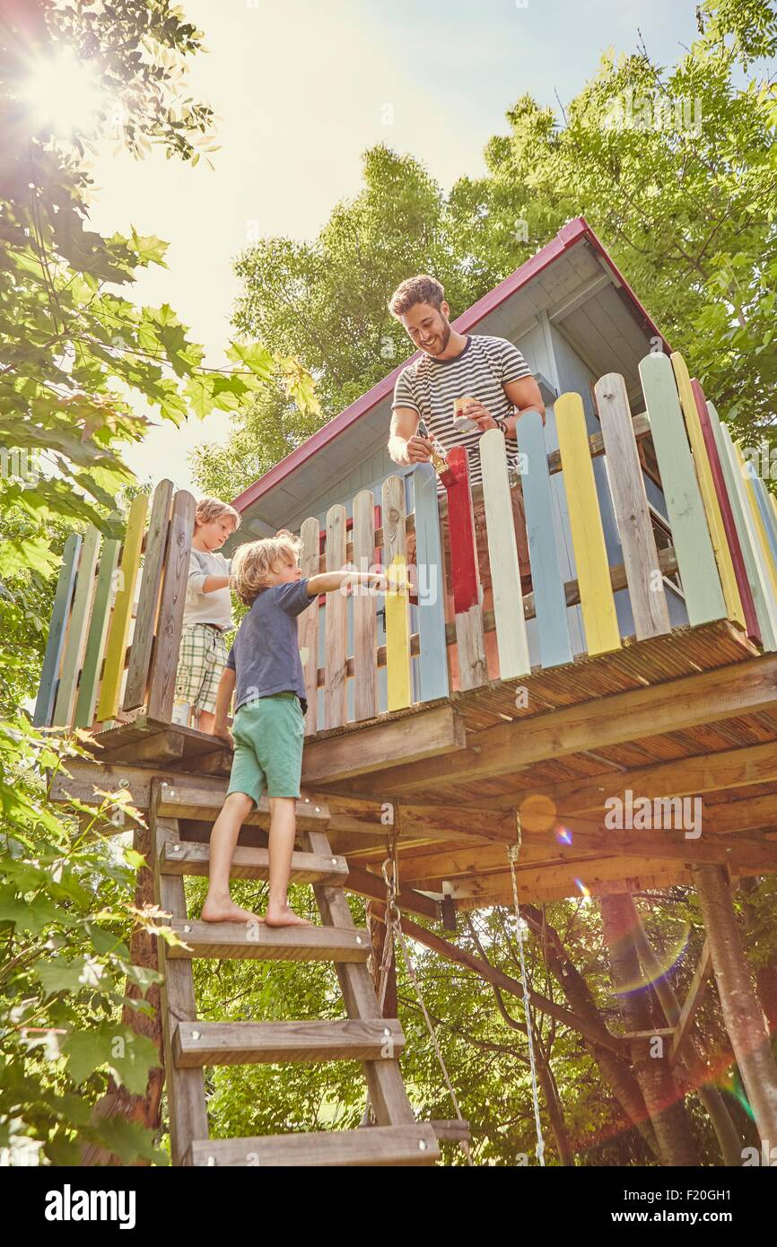 Father and two sons, painting tree house - Stock Image