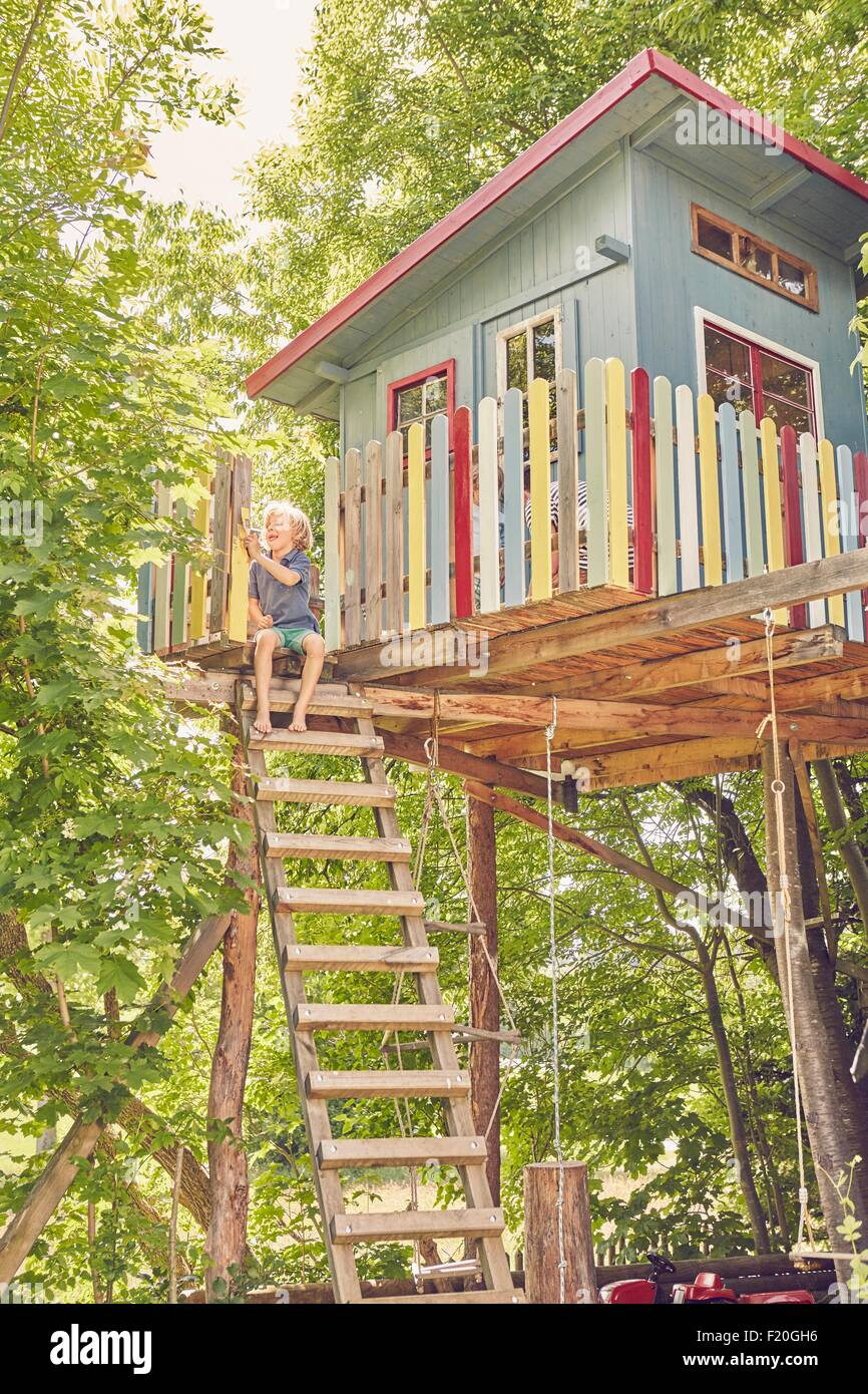 Young boy painting tree house - Stock Image