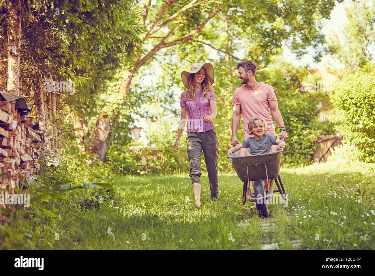 Young family outdoors, father pushing son in wheelbarrow - Stock Image