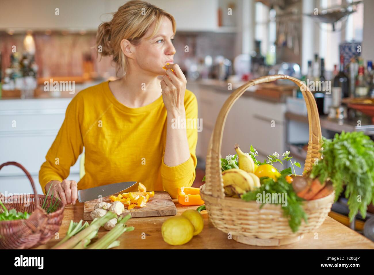 Mature woman sitting at kitchen table, chopping vegetables - Stock Image