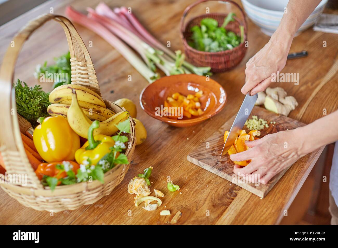 Mature woman chopping vegetables, focus on hands - Stock Image