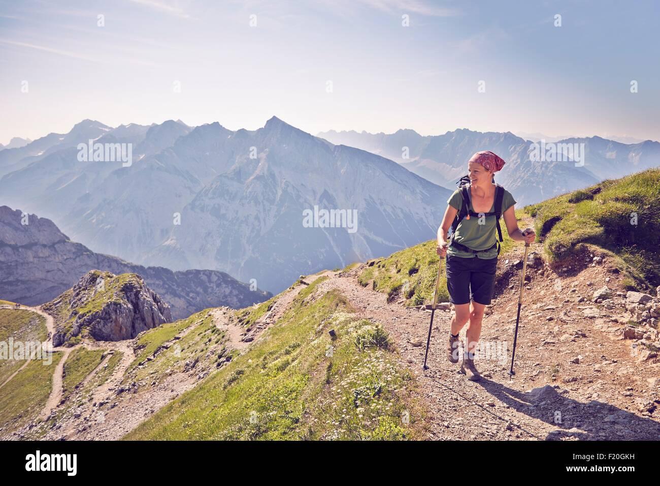 Mature woman hiking along mountain path, Karwendel-Mittenwald, Bavaria, Germany - Stock Image