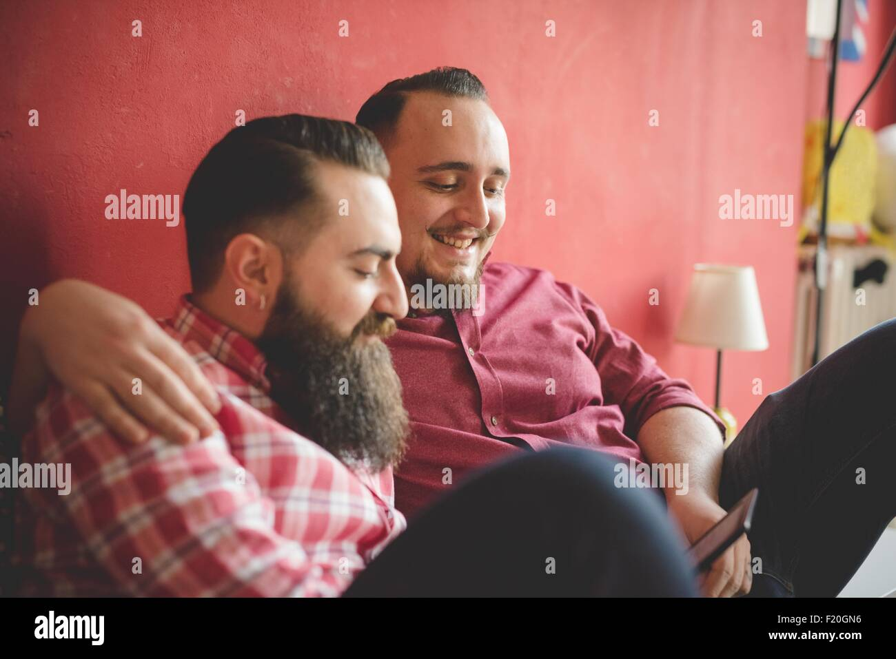 Gay couple using smartphone in bedroom - Stock Image