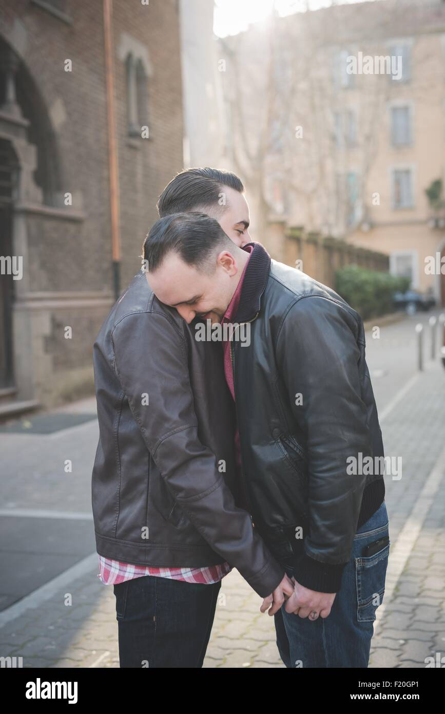 Gay couple holding hands and hugging on street - Stock Image