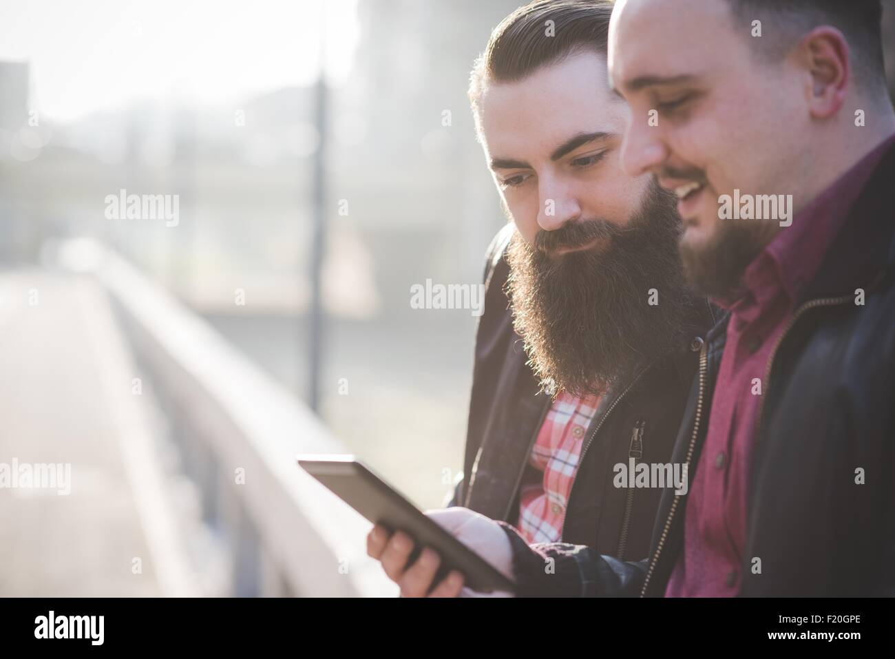 Gay couple using smartphone on pavement Stock Photo