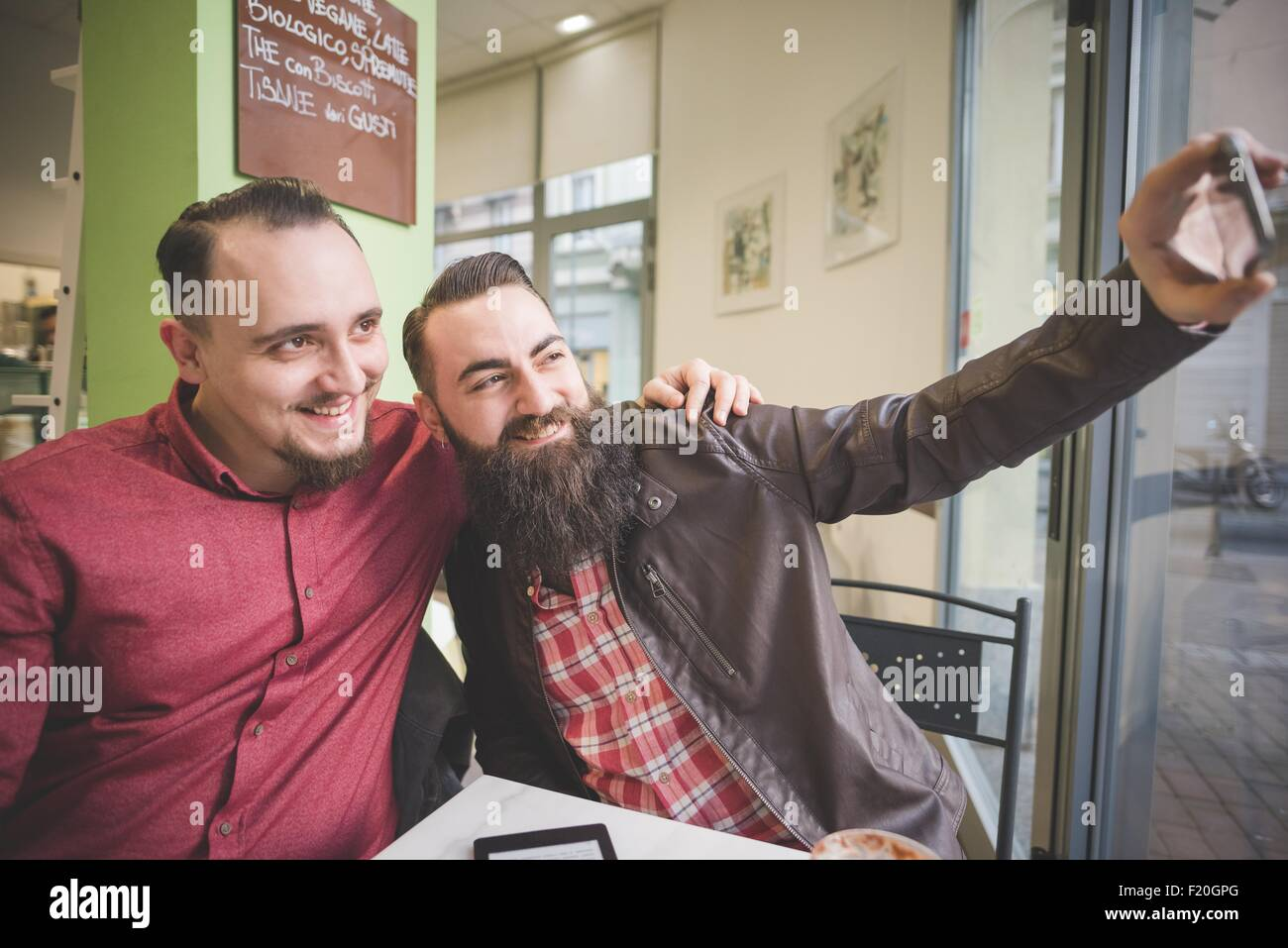 Gay couple taking selfie in cafe - Stock Image