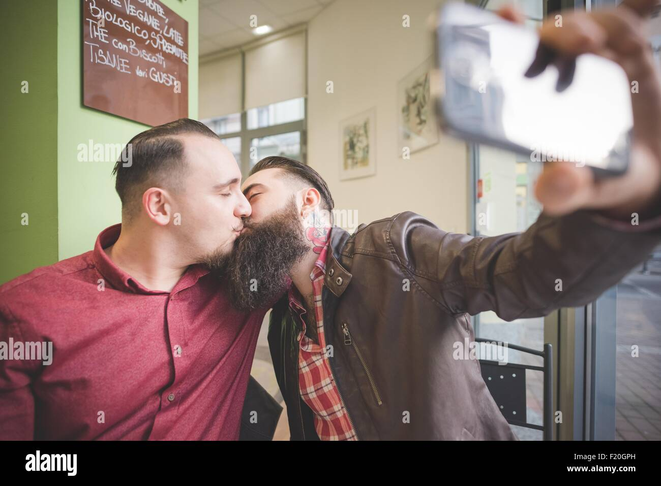 Gay couple taking selfie and kissing in cafe - Stock Image