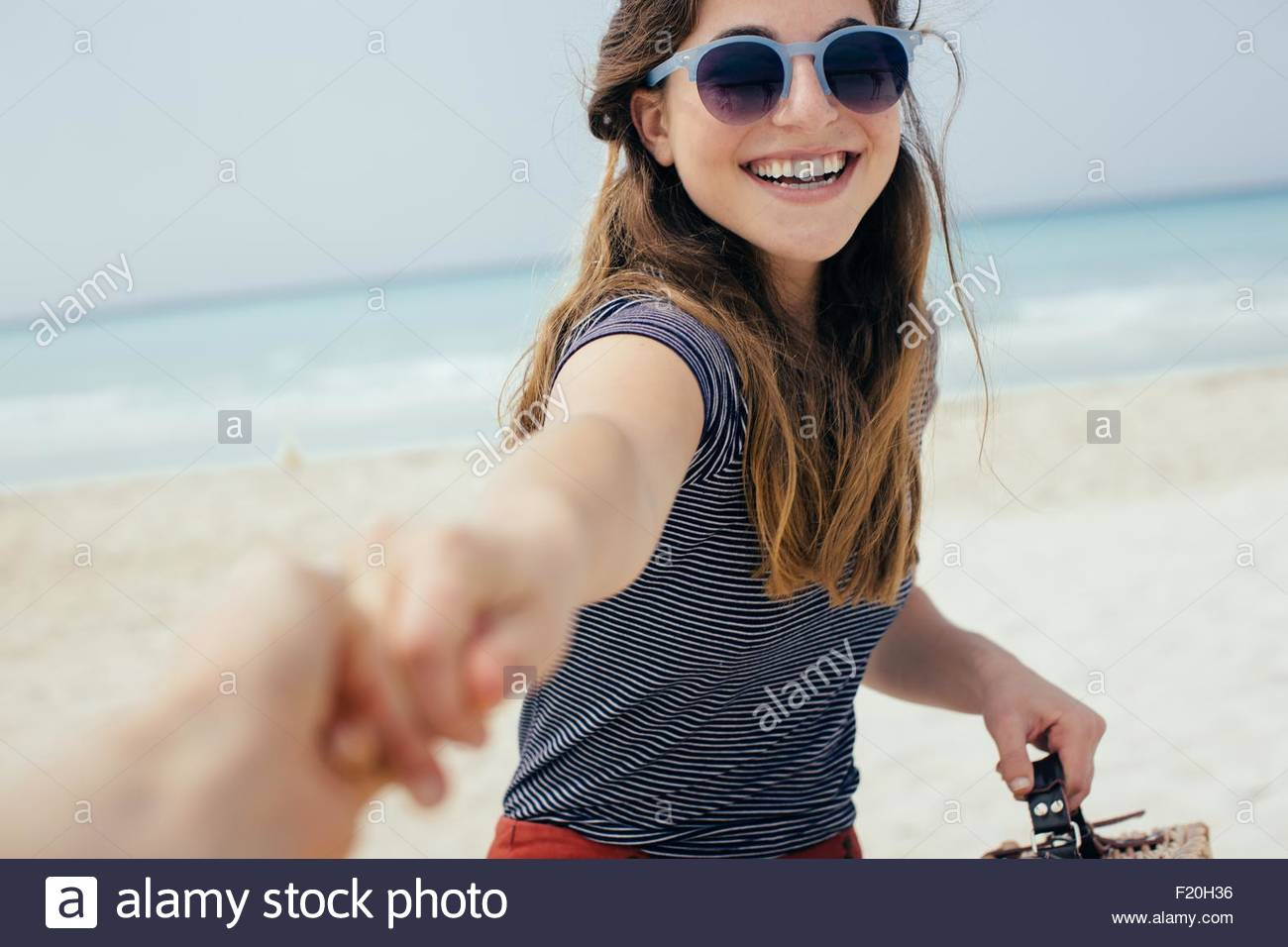 Portrait of young woman holding best friends hand on beach - Stock Image