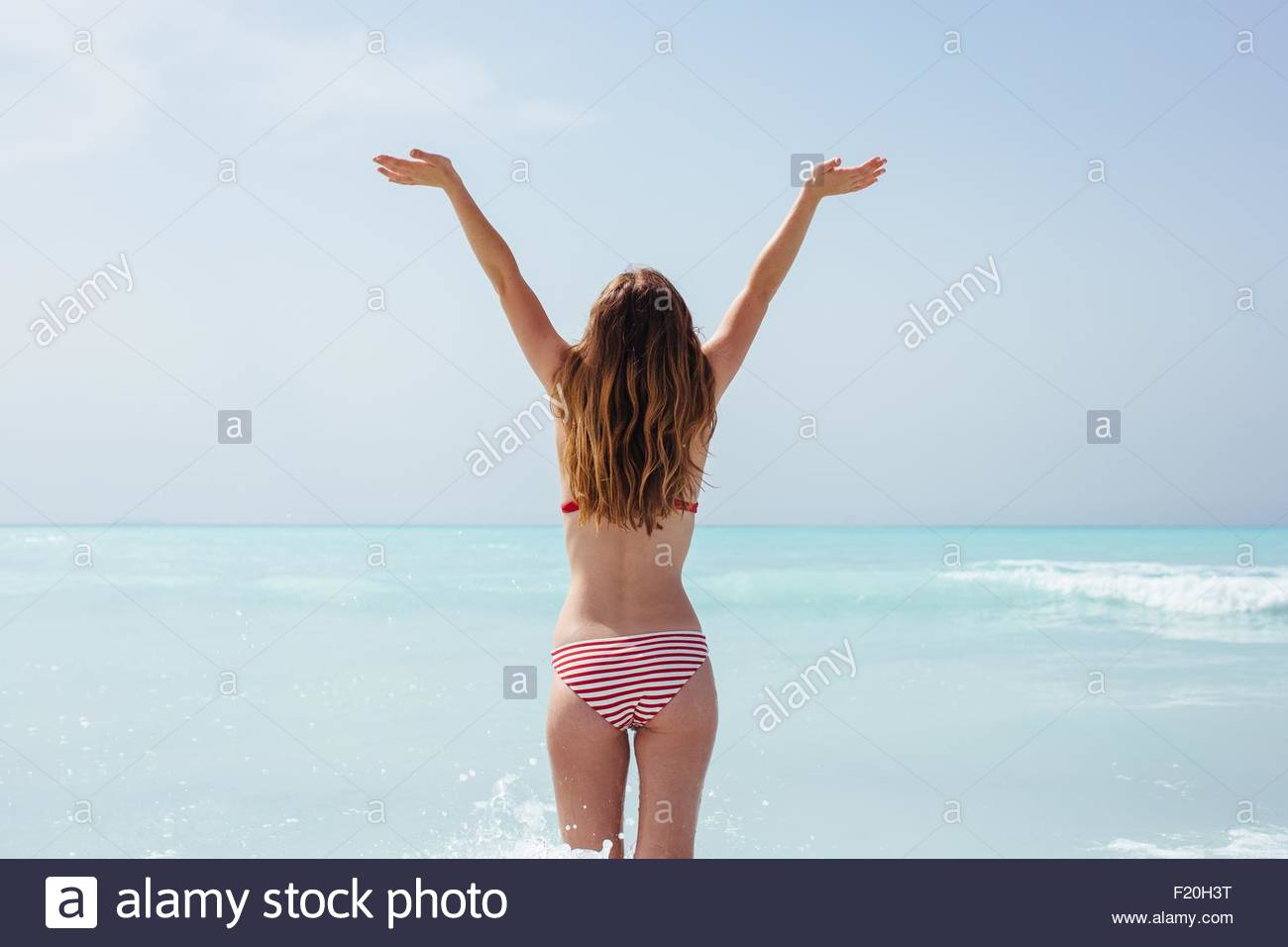 Rear view of young woman wearing bikini with arms raised in sea - Stock Image