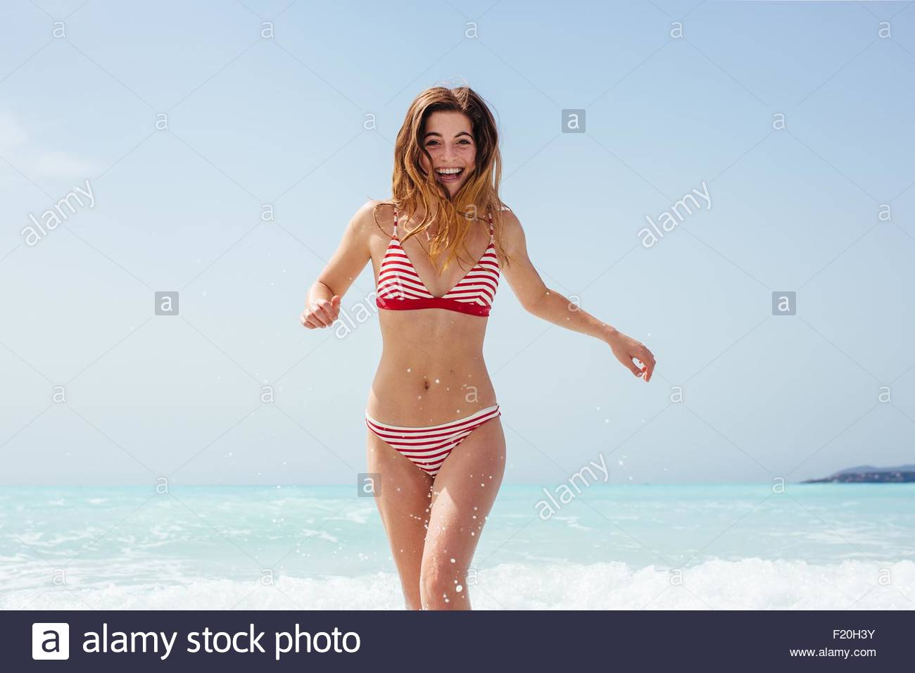 Portrait of young woman wearing bikini running in sea - Stock Image